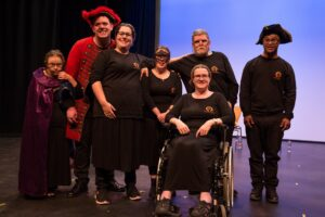 Seven people dressed in black and red on stage smiling